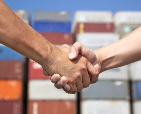 Two people shaking hands, with freight containers in the background