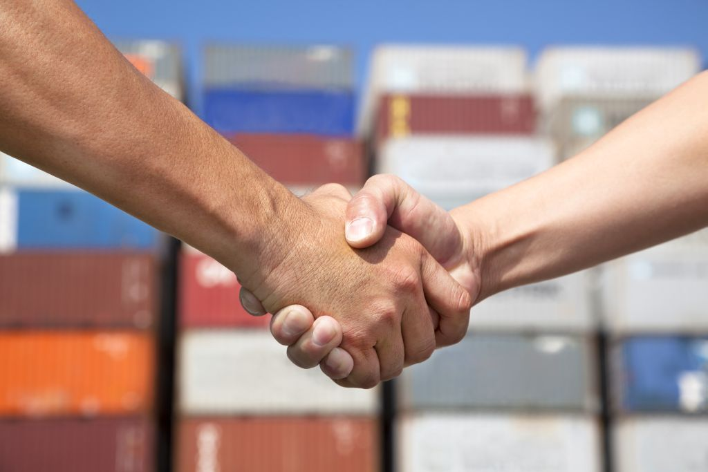 Two people shaking hands to represent agreeing to trade agreements.
